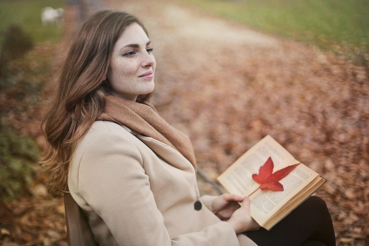 Őszi avarral borított út melletti padon ülő nő olvas.