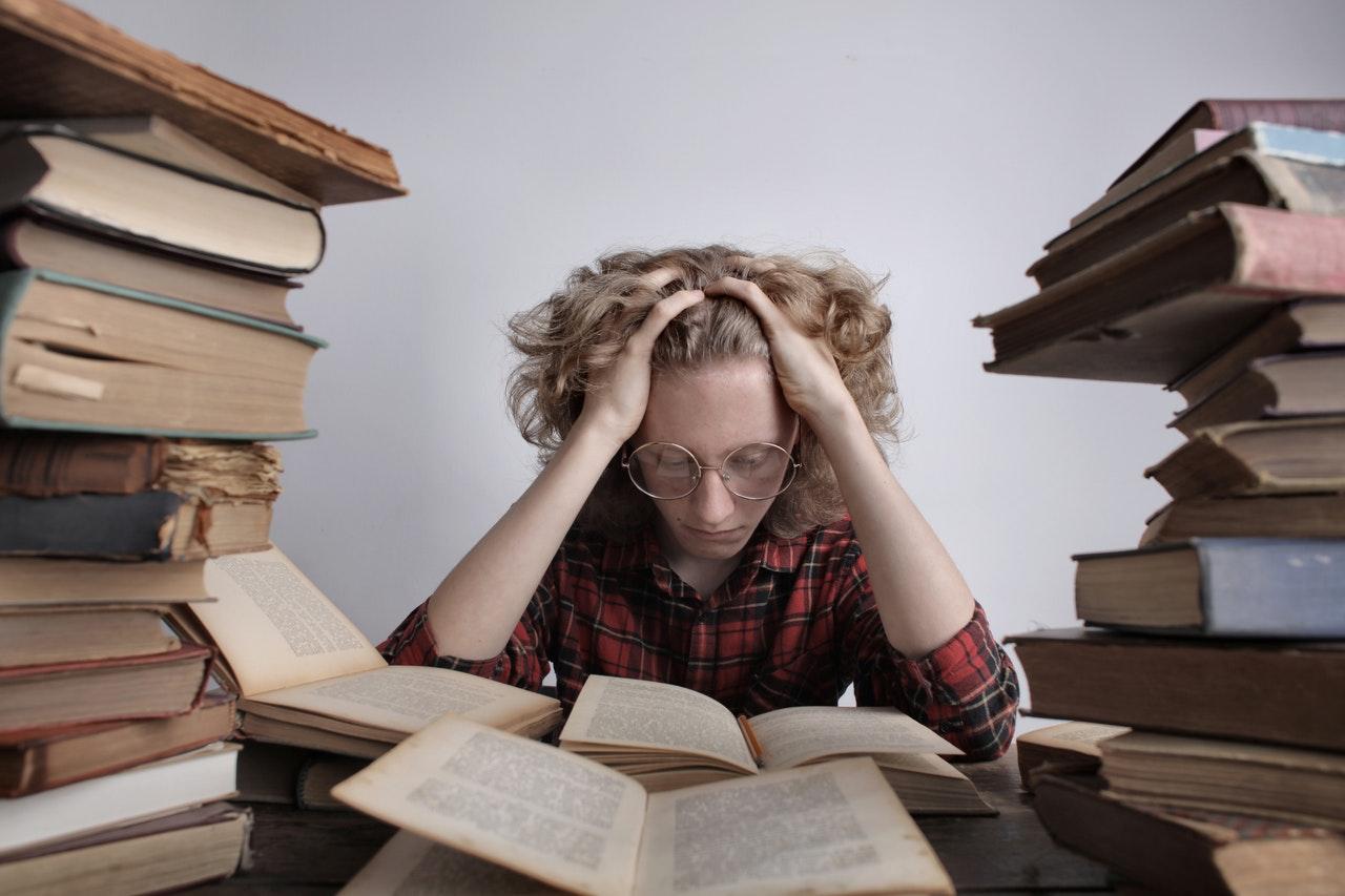 könyvek felett görnyedő tanuló